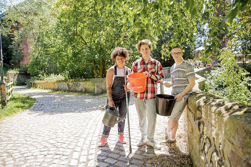 Drei junge Leute stehen mit Rechen und Eimer in einer Gartenanlage