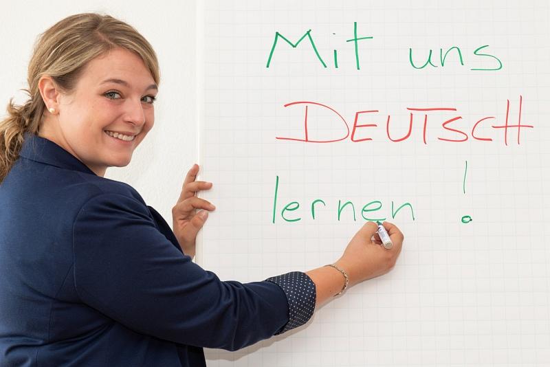 Junge Frau zeigt grinsend auf die Schrift: Mit uns Deutsch lernen