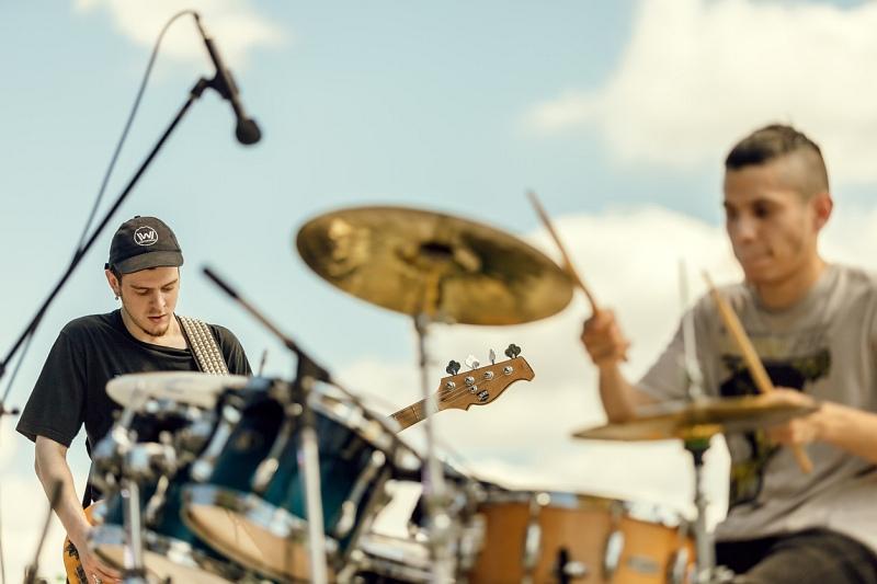 Ein junger Mann spielt Schlagzeug, dahinter steht einer mit einer E-Gitarre
