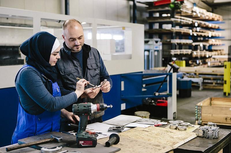 Montagehalle: Eine Frau mit Kopftuch und in blauer Latzhose zeigt einem Mann mit Halbglatze etwas an einer Werkbank