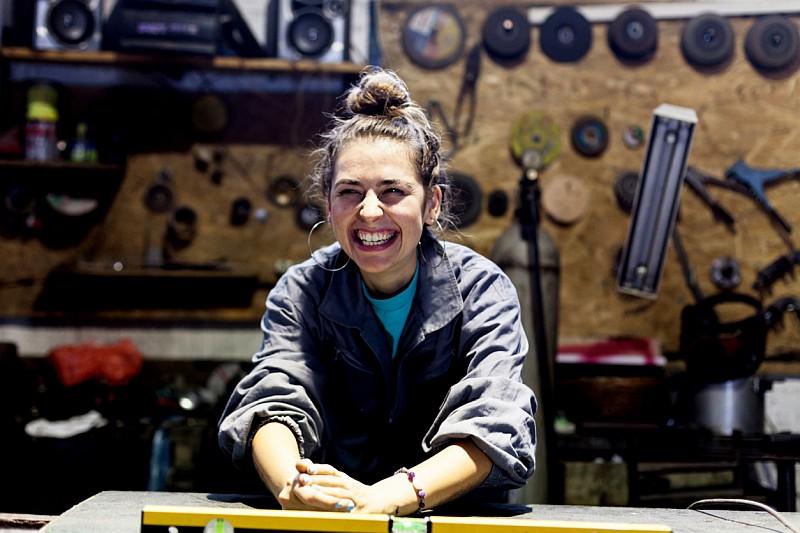 Junge Frau in Arbeitskleidung sitzt an einer Werkbank und strahlt übers ganze Gesicht