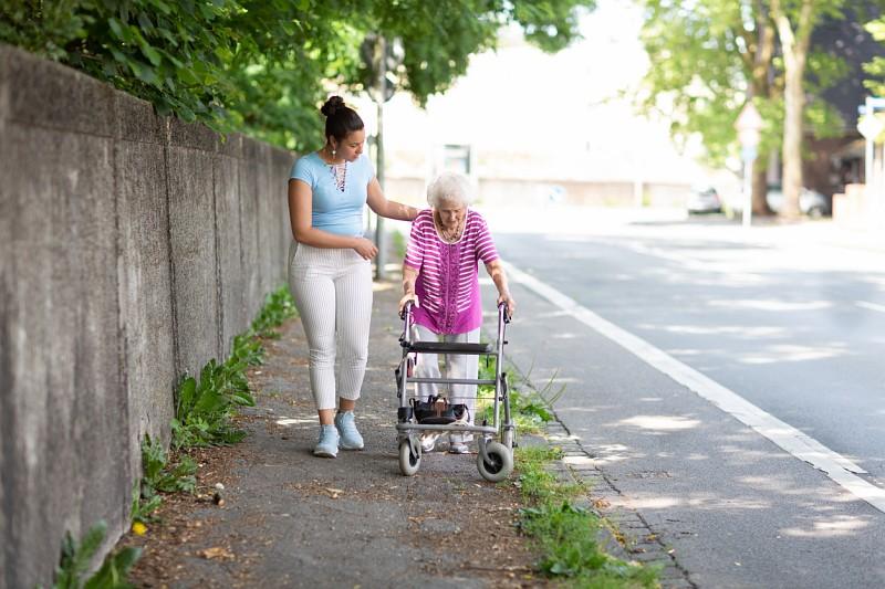 Einsame Wohnstraße: Junge Frau in heller Kleidung unterstützt einer ältere Dame, die mit einem Rollator läuft