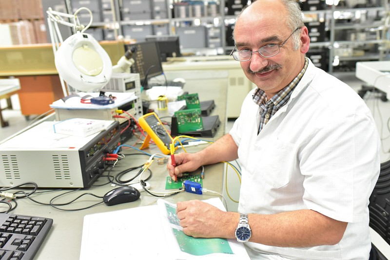 Älterer Mann arbeitet mit elektrischem Prüfgerät an Werkstück