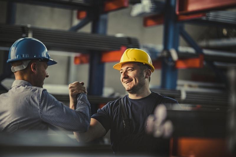 Lagerhalle für Baumaterialien: Zwei Männer mit Arbeitsschutzhelmen begrüßen sich freudig mit Handschlag.